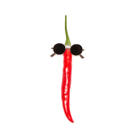 Red chili pepper in sunglasses isolated on white background. Cool guy, party goer funny minimal concept