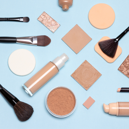Basic makeup products flatlay. Concealer, primer, liquid fluid and cream foundation with correcting, bronzing, highlighting powder, make-up brushes and sponges