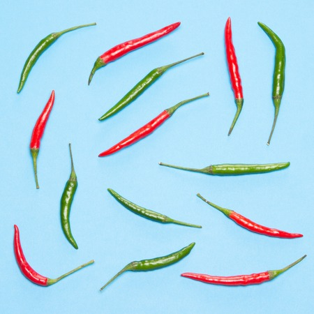 Red and green chili peppers on blue background. Bright food pattern. Top view, flat lay
