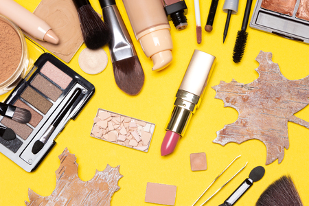 Autumn make up flat lay. Beauty products for natural makeup with maple leaves made of bark on yellow. Top view