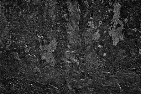 Old shabby concrete wall. Black threadbare cement surface texture. Dark grunge background Imagens