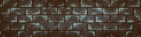 Wide panoramic dark brick wall texture. Spacious gray stone blocks masonry. Retro grunge brickwork background