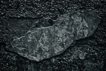 Black concrete wall with fallen off cement coating. Dark gray gloomy grunge background