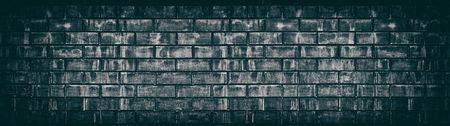 Wide old black shabby brick wall texture. Dark aged masonry panorama. Brickwork panoramic grunge background