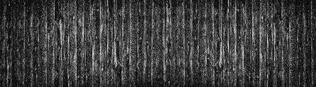 Wide old black knotty wood texture. Dark plank rough surface panorama. Wooden board panoramic background