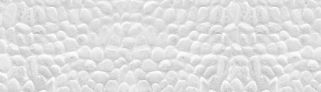 Whitewashed stone wall wide panoramic texture. White painted stones panorama. Long light background Фото со стока