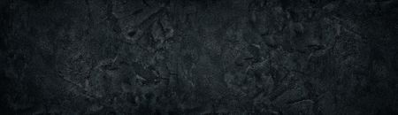 Black rough concrete wall wide texture. Fine textured cracked cement plaster surface panorama. Dark gray panoramic grunge background Standard-Bild