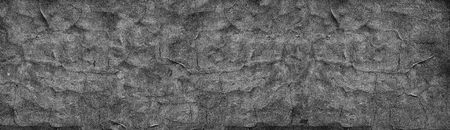 Black cracked concrete wall wide texture. Fine textured old cement surface panorama. Dark gray panoramic retro background