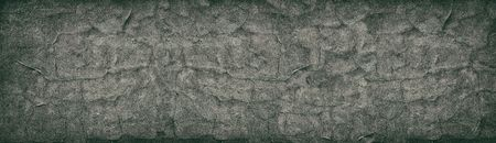 Dark cracked concrete wall wide retro texture. Aged cement surface horizontal panorama. Panoramic vintage background