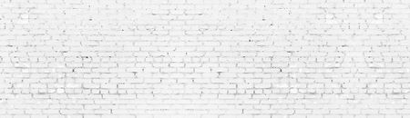 Whitewashed shabby brick wall wide panoramic texture. White painted old brickwork panorama. Long light background Фото со стока