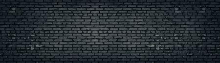 Wide old dark gray shabby brick wall texture. Black masonry panorama. Brickwork panoramic grunge background