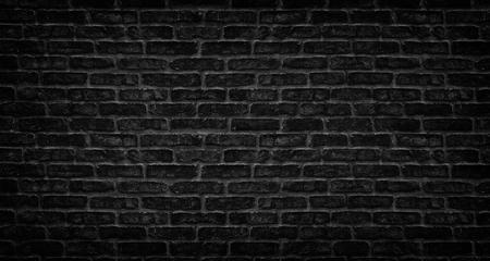 Black brick wall texture. Aged stone block masonry. Dark gloomy background Фото со стока