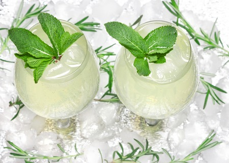 Chilled drink with mint leaves in glass cocktail goblets on ice cubes. Summer beverage. Bar menu. Cold mojito. Refreshing lemonade