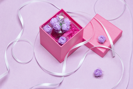 Open gift box with perfume. Fragrance as present for woman concept