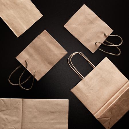 Paper merchandise bags on black background, flat lay Фото со стока