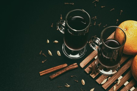 Mulled wine with spices and oranges on black table background. Retro still life with copy space Фото со стока