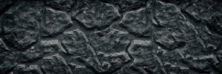 Black aged stone wall wide texture. Dark rough surface large background