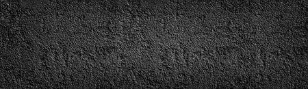 Black painted stone wall wide texture. Dark coarse pebbledash panoramic background