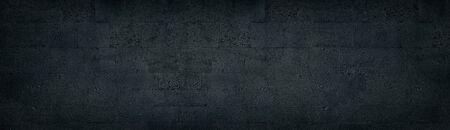 Black tuff brick wall wide texture. Dark rough stone block masonry panoramic background Фото со стока