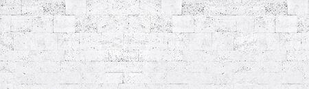 White washed tuff brick wall wide texture. Whitewashed rough stone block masonry panoramic background Фото со стока