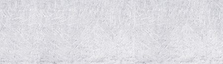 White old stamped concrete wall wide panoramic background. Whitewashed aged rough cement surface texture