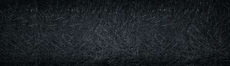 Black old stamped concrete wall wide panoramic background. Dark aged cement surface texture
