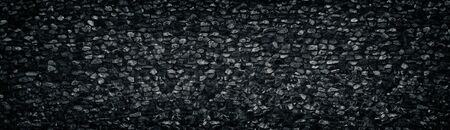 Black crushed granite stone wall wide texture. Angular rock surface panorama. Dark panoramic background Фото со стока - 126762242