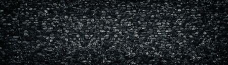 Black crushed granite stone wall wide texture. Angular rock surface panorama. Dark panoramic background Фото со стока