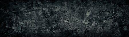 Wide weathered cracked black concrete wall. Black broken cement surface texture. Dark gloomy grunge background