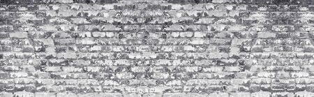 Wide light gray shabby brick wall texture. Old masonry with peeling white paint. Weathered brickwork panoramic vintage background Фото со стока