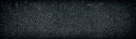 Black old concrete wall wide texture. Rough cement surface long panorama. Dark gray gloomy grunge panoramic background