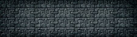 Black patterned tile wall wide texture. Dark masonry long backdrop. Gloomy gothic background