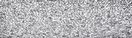 Light gray stone wall wide texture. Rough white rock panoramic vintage background