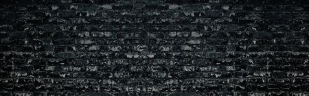 Wide black shabby brick wall texture. Old masonry large creepy backdrop. Dark weathered brickwork gloomy grungy background Фото со стока - 132024353