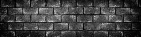 Wide dark concrete brick block wall. Black shabby long texture. Panoramic gloomy grunge background
