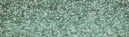 Teal natural stone wall wide texture. Rough rock panoramic retro background. Long vintage backdrop