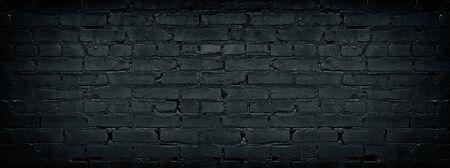 Wide black brick wall texture. Dark old masonry background. Rough brickwork