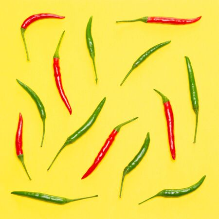 Red and green chili peppers on yellow background. Bright food pattern. Top view, flat lay Фото со стока