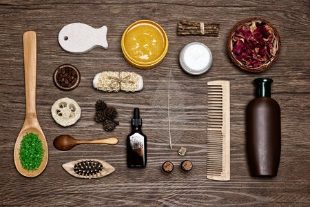 Natural body and hair care cosmetics on wood background. Spa products and accessories. Top view, flat lay