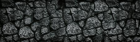 Natural granite stone wall wide texture. Dark rock masonry widescreen gloomy gothic background Фото со стока - 132024563