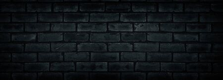 Old shabby black brick wall texture. Cement block dark widescreen backdrop. Gloomy grunge wide background