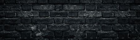 Black rough brick wall close-up wide texture. Old dark masonry panorama. Gloomy grunge widescreen background