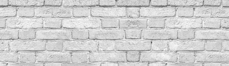 Light gray brick wall close-up wide texture. Old rough stone block whitewashed background