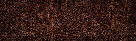 Rough bronze colored surface widescreen background. Dark cement plaster wide texture