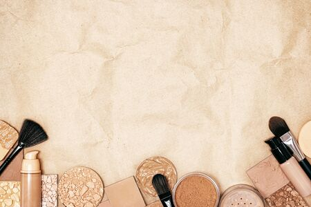 Makeup products to even skin tone and complexion on kraft paper - top view. Makeup primer, foundation, powder with make-up brushes, copy space 写真素材