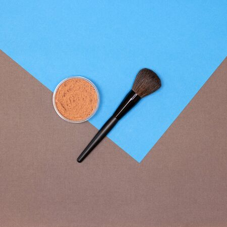 Loose makeup powder with make-up brush flatlay on blue and brown background 写真素材