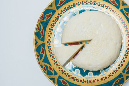 Traditional Russian Adygei cheese served on hand-painted plate isolated over white background