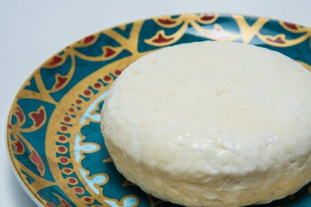 tradition: Traditional Russian Adygei cheese served on hand-painted plate isolated over white background