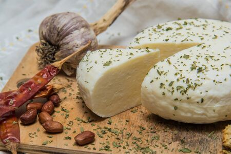 Traditional Russian Adygei cheese with red peppers and garlic served on wooden cutting board