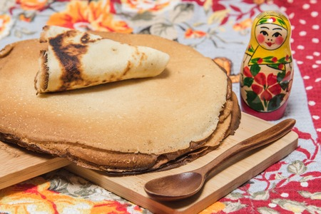 Buttercakes traditional for Russian pancake week and Russian nesting doll on wooden cutting plate